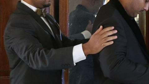 witness helps the groom to wear Footage