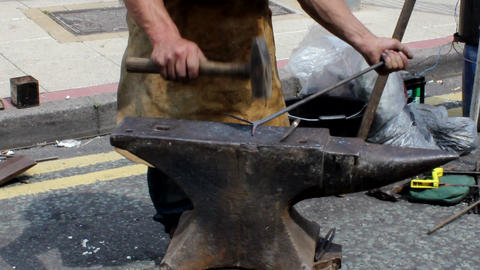 Blacksmith forges a piece of metal on the anvil Stock Video Footage