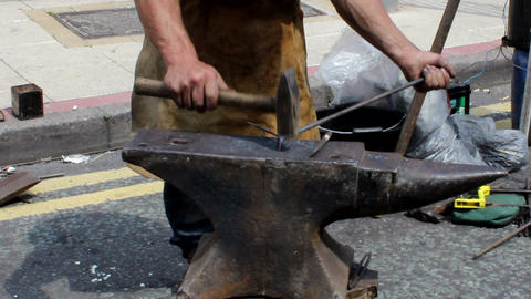 Blacksmith forges a piece of metal on the anvil Footage