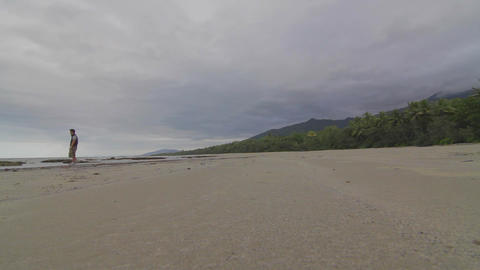 a wide low angle of man walking in distance at a b Footage
