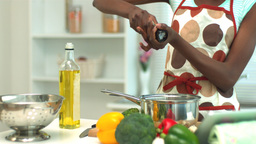 Woman adding pepper to saucepan Footage