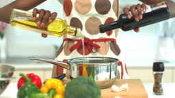 Woman adding oil and vinegar to saucepan Footage