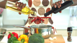Woman adding oil and vinegar to saucepan Stock Video Footage