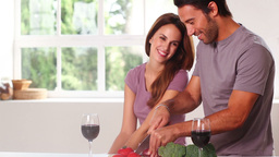 Smiling couple with red wine chopping vegetables Stock Video Footage
