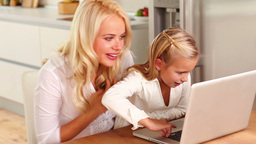 Mother and daughter using laptop at kitchen table Stock Video Footage