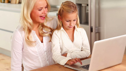 Mother and daughter using laptop at kitchen table Footage