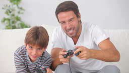 Father and son playing video games together Stock Video Footage