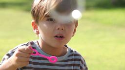 Little boy has fun blowing bubbles Footage