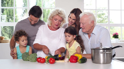 Granny cutting vegetables with the family around Footage