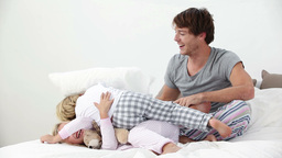 Father and his children playing in bed Stock Video Footage