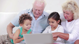 Two grandparents and two children using a laptop Footage