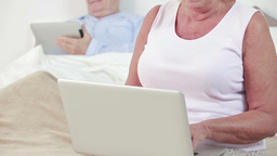 Old couple using a laptop and tablet Stock Video Footage