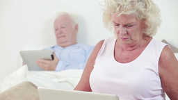 Old couple using a laptop and tablet Footage