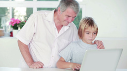 Child using a laptop with his grandpa Stock Video Footage