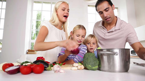 Posing family putting vegetables in a pot Footage