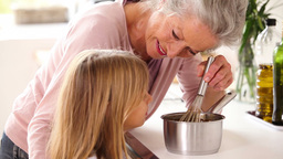 Granny and little girl making chocolate sauce toge Footage