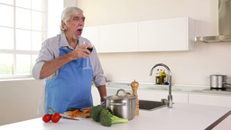 Elderly man peeling carrots and drinking red wine Stock Video Footage