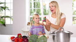 Mother and her daughter juggling with vegetables Stock Video Footage