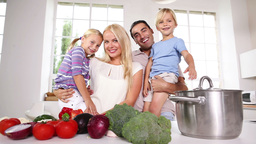 Children in their parents arms in the kitchen Stock Video Footage