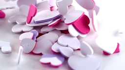 Many pink heart confetti dropping on the floor Footage