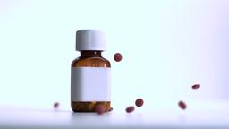 Red pills falling beside jar Footage