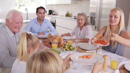 Mother serving carrots to son at family dinner Footage