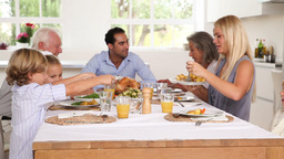 Mother serving roast potatoes to son at family din Footage