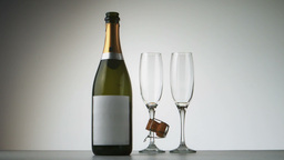Champagne cork falling in front of bottle and flut Footage