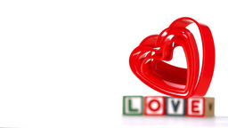 Heart Ornaments Falling With Blocks Spelling Love  stock footage