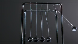 Finger pushing newtons cradle Stock Video Footage