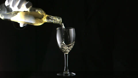 Gloved hand pouring white wine into glass Footage