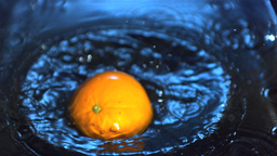Orange falling into water Footage