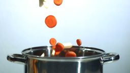 Chopped carrot and parsnip falling into saucepan Stock Video Footage