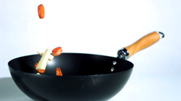 Chopped carrots and parsnips falling into wok Footage
