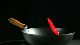 Red chili falling into a wok Footage
