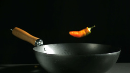 Jalapeno chili falling into a wok Stock Video Footage