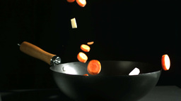 Chopped carrots and parsnips falling into a wok Stock Video Footage