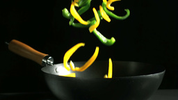 Mixed peppers falling into a wok on black backgrou Stock Video Footage