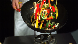 Chef tossing mixed vegetables in wok ビデオ