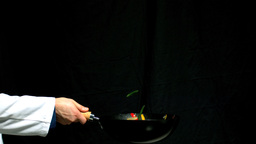 Chef tossing vegetables in a wok black background ビデオ