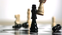 Hand knocking over black chess piece with white on Footage