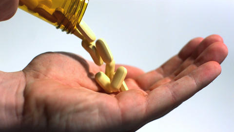 Large pills being poured into hand on white background Footage