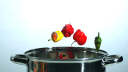 Various chilis falling in a pot Stock Video Footage