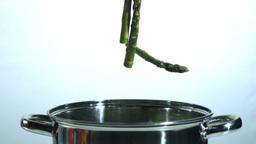 Asparagus stalks falling into a saucepan Footage