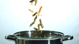 Tricolour fusilli falling into a saucepan Stock Video Footage
