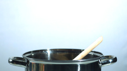 Wooden spoon falling into a saucepan Footage