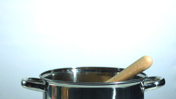 Wooden spoon falling in a pot Stock Video Footage