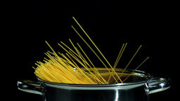 Spaghetti falling in pot on black background Footage