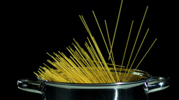 Spaghetti falling in pot on black background Stock Video Footage
