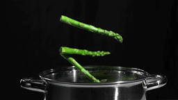 Asparagus falling in pot on black background Footage